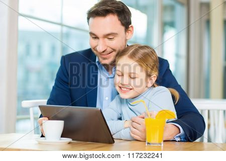 Happy father and daughter at cafeteria with tablet.