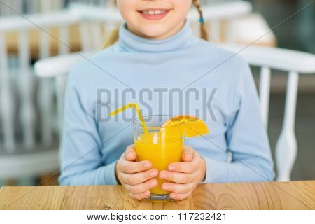 Smiling girl holding orange juice.