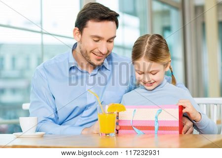 Young father and cute daughter staring at the present.