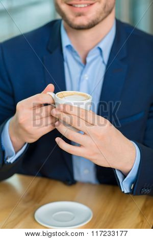 Good-looking young man holding coffee mug.