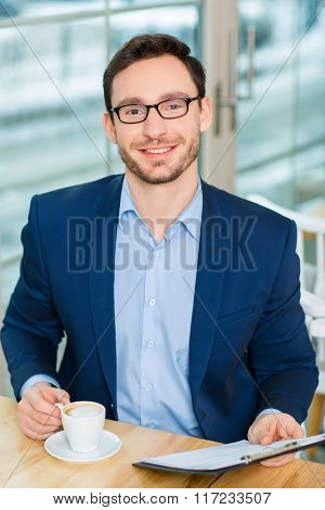 Handsome young businessman sitting at the cafeteria.