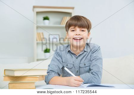 Beautiful happy child smiling while doing homework