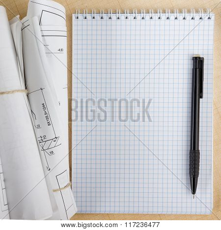 Architectural blueprints and blueprint rolls on white background.