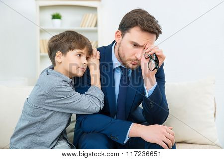 Father is feeling worry while son trying to comfort him