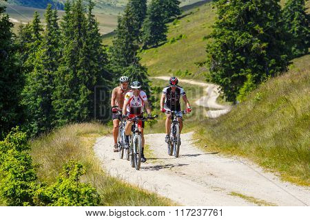 Rodna Mountains, Romania, 05 July 2015: Three Cyclists Riding Mountain Bike In Sunny Day On A Mounta
