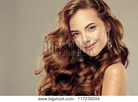 Beautiful girl with long wavy hair .  Brunette with curly hairstyle