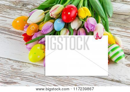 Colorful tulips with eggs on wooden table. Top view.