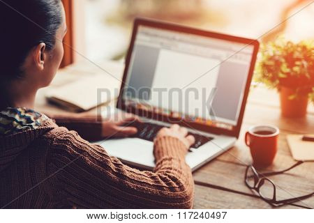 Working at home. Close-up image of young woman working on laptop while sitting at the rough wooden table ** Note: Soft Focus at 100%, best at smaller sizes