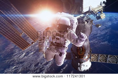 International Space Station with astronauts over the planet Earth. Elements of this image furnished
