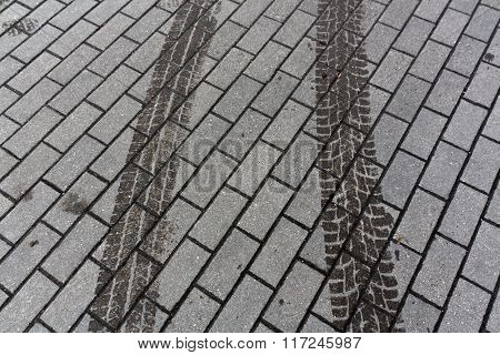 Wet Car Tracks On Pavement.
