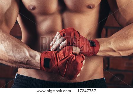 Muscular Fighter With Red Bandages against the background of a brick wall