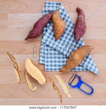 Peeled Two Varieties Of Sweet Potatoes With Peeler On Rustic Wood Table.