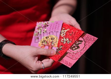 Red Envelope With Blessing Words For Chinese New Year Gifts Held In Hand, Traditional Celebration, C