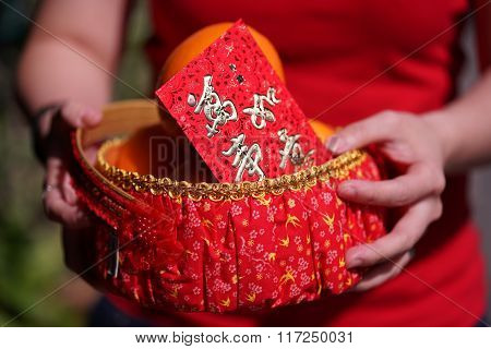 People Held The Orange Basket With Blessing Red Envelope For Chinese New Year Gifts, The Word Is May