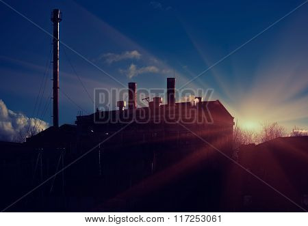 Silhouette of power plant on evening background of setting sun