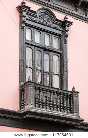 wooden balcony and a window on pink building