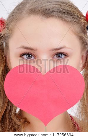 Close-up Portrait Of A Pretty Teenage Girl Keeping Paper Heart In Front Of Her Face
