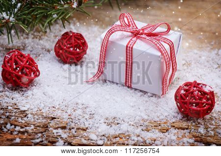 Christmas Gift Box On Snowy Wooden Background