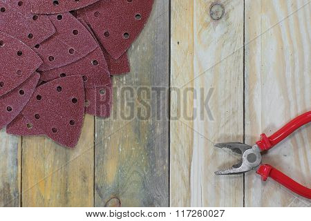 Triangle Sand Papers On Wooden Boards With Pliers Horizontally