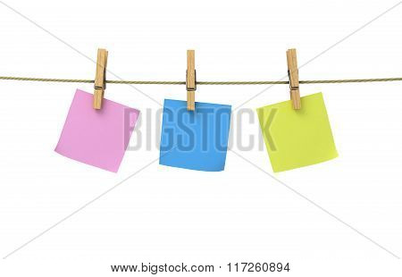 Sheets Of Paper Of Different Colors On Clothespins Attached To A Rope