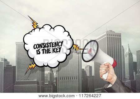 Consistency is the key text on speech bubble and businessman hand holding megaphone