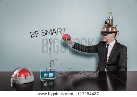 Be smart concept with businessman holding brain