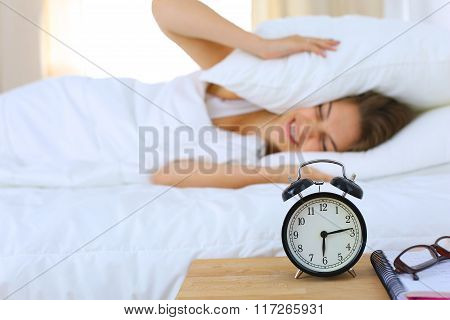 A young woman putting her alarm clock off in the morning