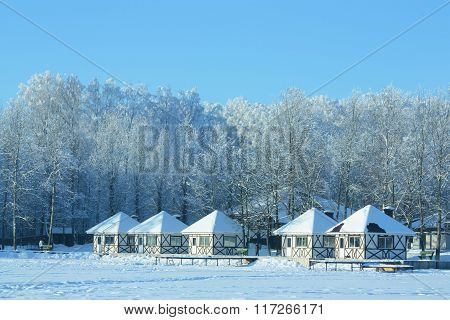 Small Houses In Snow On Frozen Lake