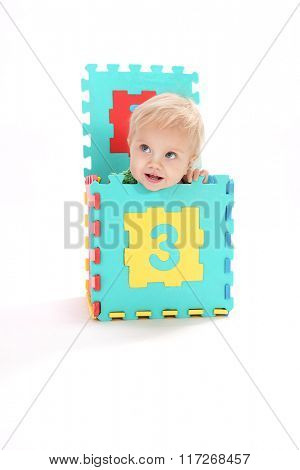 little child baby smiling isolated on white background studio shot playing studding learning numbers count sitting in the box