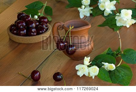 brown clay jug and ripe cherry