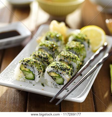 green themed veggie sushi roll on plate with avocado, kale and cucumber