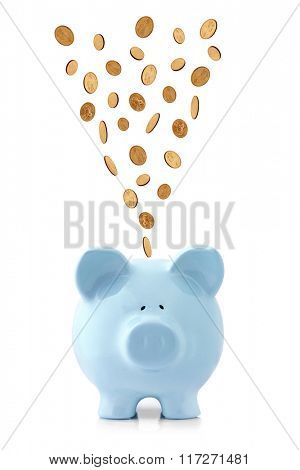 Golden coins falling into a blue piggy bank, isolated on white.  US dollar coins