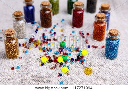 The Beads Scattered On The Table And In Jars.