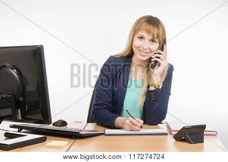 Business Woman Talking On The Phone, Writing In A Notebook, And Looked Into The Frame