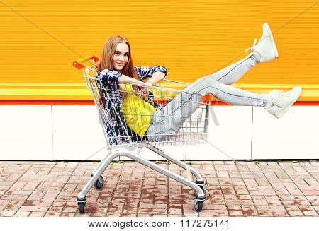 Fashion Cool Girl Having Fun Sitting In Shopping Trolley Cart Over Colorful Background