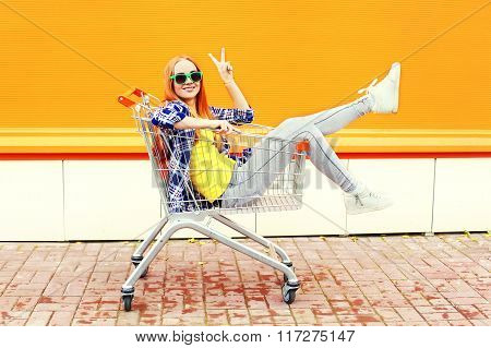 Fashion Cool Smiling Girl Having Fun Sitting In Shopping Trolley Cart Over Colorful Background
