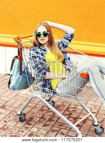 Fashion Pretty Girl Wearing A Sunglasses Sitting In Shopping Trolley Cart Over Colorful Background