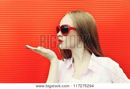 Pretty Woman In Red Sunglasses Sends An Air Kiss Over Colorful Background