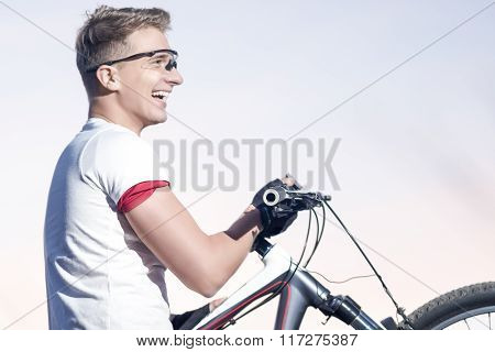 Cycling And Sport Concepts. Caucasian Cyclist Sportsman  With Mounting Bike Outdoors.