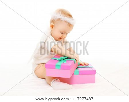 Baby Playing With Gift Boxes On A White Background