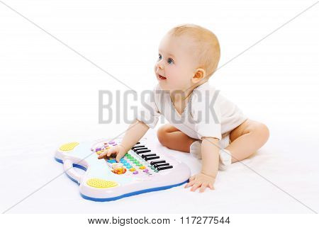 Cute Baby Playing With Toy Piano On A White Background