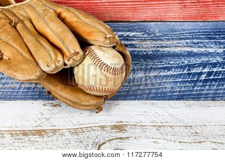 Old Worn Baseball Mitt And Ball On Faded Boards Painted In American National Colors