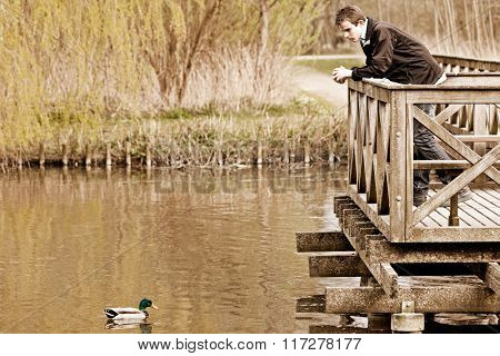 Teenage Boy Standing Watching A Duck