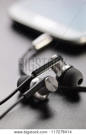 Smartphone And Earphones On Table