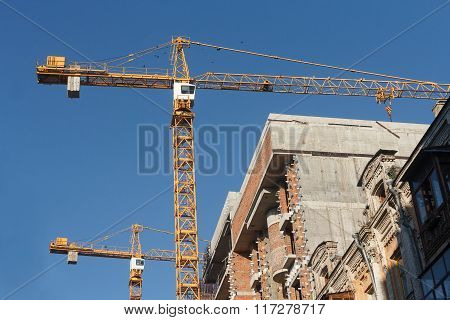 Two Construction Cranes And House Under Construction. Industry
