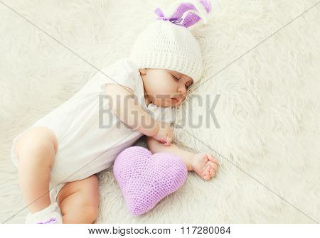 Cute Baby Sleeping On White Bed At Home With Knitted Pillow Heart Shape