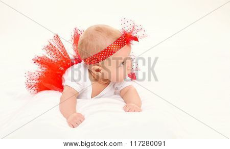 Cute Little Baby Girl Lying In Red Skirt On Bed