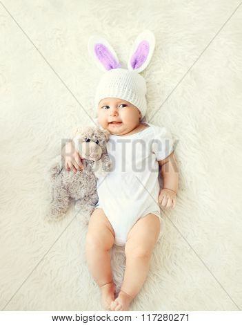 Happy Sweet Baby In Knitted Hat With A Rabbit Ears And Teddy Bear Toy Lying On Bed, Top View