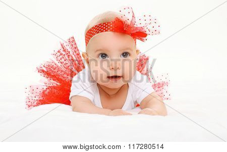 Portrait Cute Little Baby Girl Lying In Red Skirt On Bed