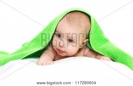 Portrait Of Little Baby Under Towel Lying On Bed